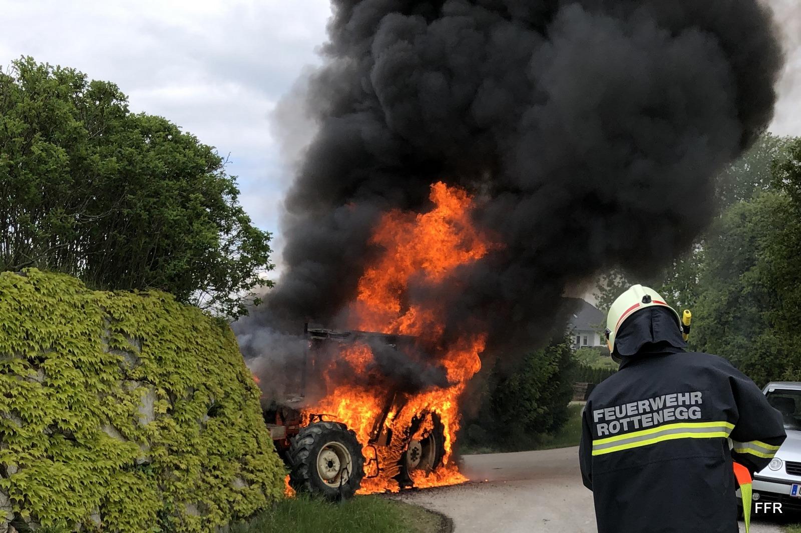 Feuerwehrmann vor brennendem Traktor